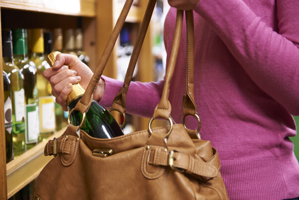 Image of a lady stealing a bottle of wine