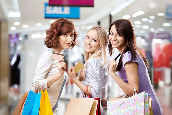 Three happy young women shopping with loyalty cards